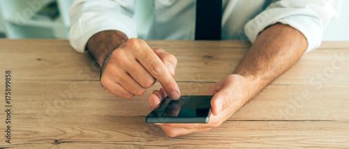 Zdjęcie XXL Smartphone w rękach pomyślny biznesmen