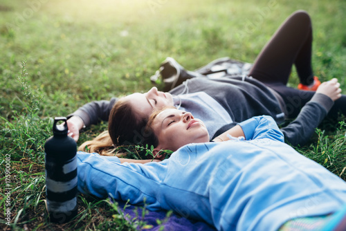 Two young sportswomen laying on grass with eyes closed relaxing after outdoor workout