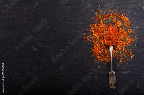 dried saffron spice in a spoon on dark background