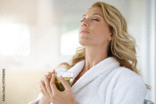 Fotografie, Obraz  Portrait of attractive 40-year-old woman in bathrobe drinking infusion