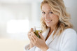 canvas print picture Portrait of attractive 40-year-old woman in bathrobe drinking infusion