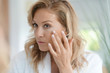 canvas print picture Portrait of attractive blond woman applying anti-aging cream