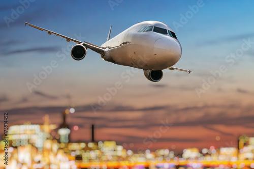 Zdjęcie XXL Samolot lata nad miastem przy zmierzchem.