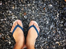 Feet Of A Man Wearing Sandals Or Flip Flops On The Old Stone Concrete Floor For Summer Time Vacation Attribute, Slippers, Shoes. Summer Holiday And Vacation Concept Vintage Tone With Copy Space.
