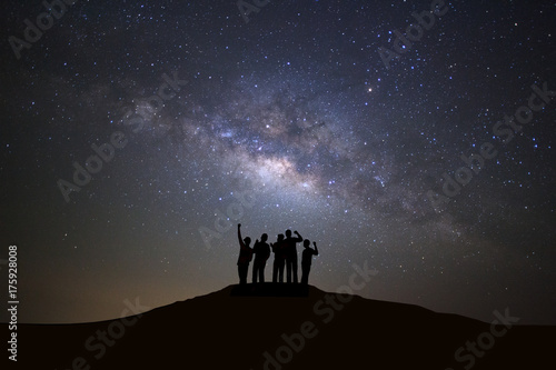 Landscape with milky way galaxy, Starry night sky with stars and silhouette of people standing happy man on high mountain.