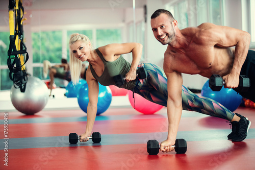 Deurstickers Fitness Young couple working out with dumbbells at gym