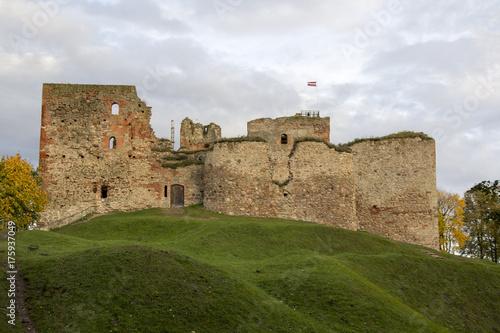 Plakat Ruiny zamku Orderu Inflant zostały zbudowane w połowie XV wieku. Bauska Łotwa jesienią. Łotewska flaga na szczycie wieży