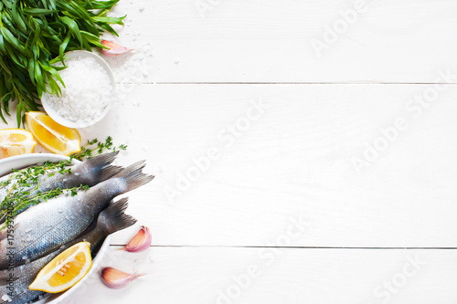 Foto op Aluminium Vis White wooden background with fresh raw fish and ingredients