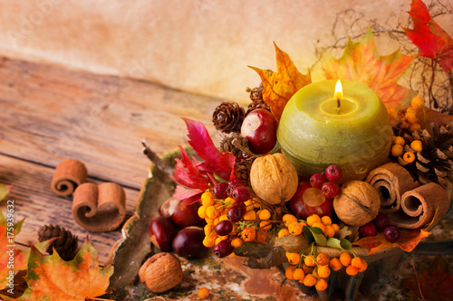 Natural autumn decoration with burning candle on rustic wooden table Canvas Print