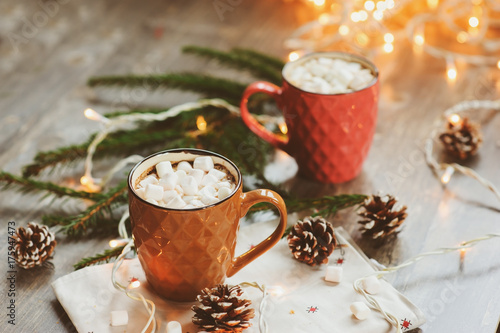 Foto op Canvas Kerstmis two mugs of hot cocoa with marshmallows on rustic wooden table with christmas lights. Cozy winter festive home concept