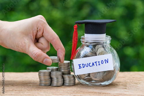 Fototapeta Woman hand holding stack of coins money and glass jar with full of coins and graduates hat label as Education, education or savings concept obraz