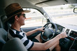 Young man with a straw hat and sunglasses driving a van on a highway