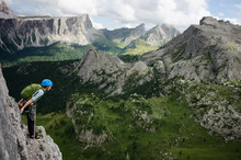 Female Rock Climber Resting On High Narrow Rock Ledge, Dolomites, Italy