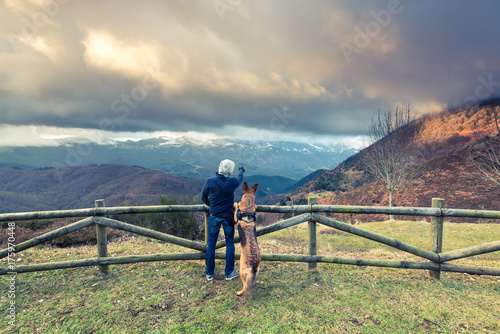 Keuken foto achterwand Ontspanning Man and dog admiring view in mountains