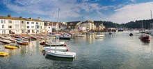 Panorama Of The Coast In The Town Of Teignmouth. Some People Rest On The Beach. Swim Boats After A Day's Work.