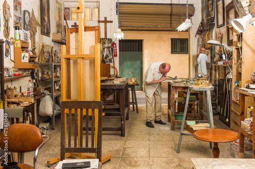 Maestro artesano trabajando en su taller de talla y restauración. Canvas Print