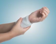 Injured Hand With Bandage On Blue Background