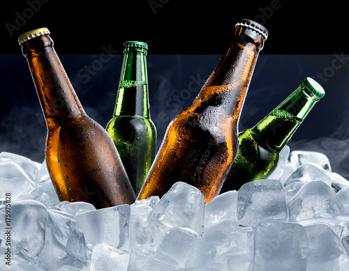 Photo  Cold bottle of beer with drops in ice cubes isolated on black background
