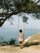 Rear view of girl on swing with view of sea
