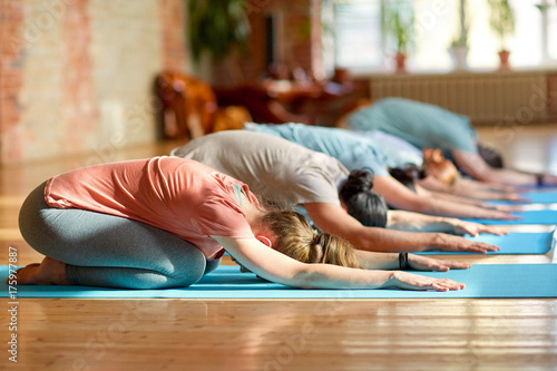 Tuinposter School de yoga group of people doing yoga exercises at studio
