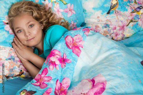 Poster Kasteel Gracious young beautiful blond girl, little princess with long hair and blue eyes, the child lies in bed, sleeps in a beautiful bedding flowers and butterflies