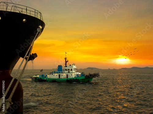 Plakat Holownik żegluje po asystowaniu dużym statkom na poboczu w porcie przemysłowym.