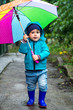 Little boy playing in rainy autumn park. Child with colorful rainbow umbrella, waterproof coat and boots jumping in puddle in the rain. Kid walking in autumn shower. Outdoor fun by any weather