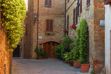 Fototapeta na wymiar Beautiful narrow street with sunlight and flowers in the small magical and old village of Pienza, Val D'Orcia Tuscany, Italy.