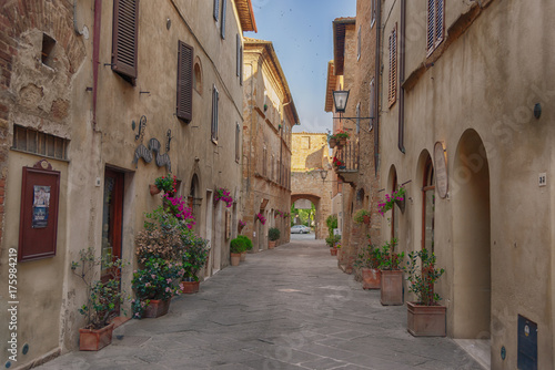 Beautiful narrow street with sunlight and flowers in the small magical and old village of Pienza, Val D'Orcia Tuscany, Italy.