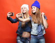 Leinwanddruck Bild - Two teenage girls friends in hipster outfit make selfie on a pho