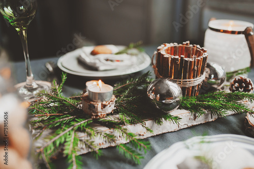 фотографія Festive Christmas and New Year table setting in scandinavian style with rustic handmade details in natural and white tones