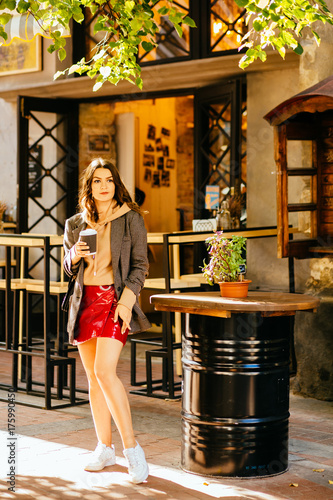 4592ea0a55b Autumn sunny lifestyle fashion portrait of young stylish hipster woman in  red skirt drinking coffee and standing near street cafe