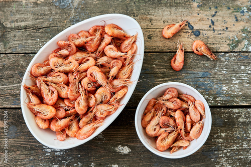 Photo  Boiled shrimps on a white dish and on an old rustic table