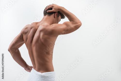 Canvas Print Rear view of charming muscular guy