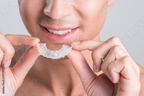 Fotografía  Positive guy is demonstrating transparent brace for teeth