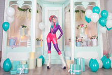 Pretty Anime Girl Wearing Latex Rubber Doll Catsuit And Posing Near Cute White Gift Shop With Air Ballons And Presents For Christmas And New Year