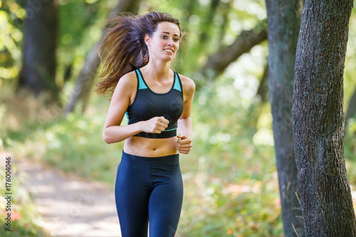 Young smiling sporty woman running in park in the morning. Fitness girl  jogging in park. Trail running concept background - Buy this stock photo  and explore similar images at Adobe Stock