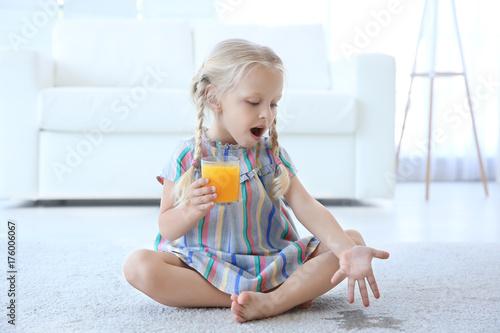 Obraz Cute little girl with glass of juice sitting on carpet near wet spot - fototapety do salonu