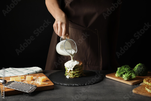 Woman pouring sauce onto tasty broccoli pancakes at table