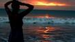 Silhouette of the woman standing next to the seaside during sunset, steadycam shot