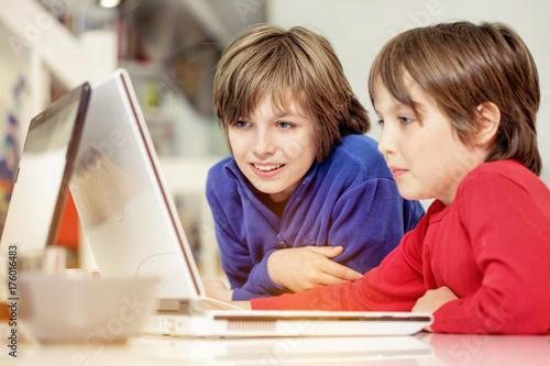Plakat Bracia w domu w stylu loftu, bawiący się w laptopach, poważni, śmiejący się, całkowicie zszokowani i zabawni
