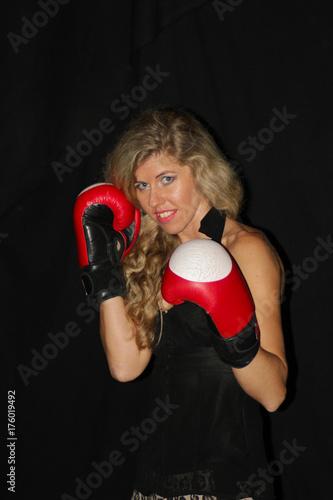 Plakat zabawna blondynka w czarnej sukience w czerwone rękawice bokserskie