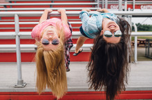 Two Girls Hanging Upside Down At Bleachers
