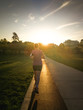 Woman running on track in park at sunset