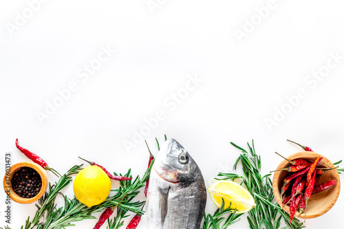 Fotografie, Obraz Preparing dorado with spices rosemary, pepper, chili, lemon