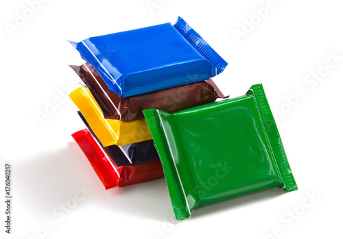 Square chocolate bars in multi-colored packaging on a white isolated background