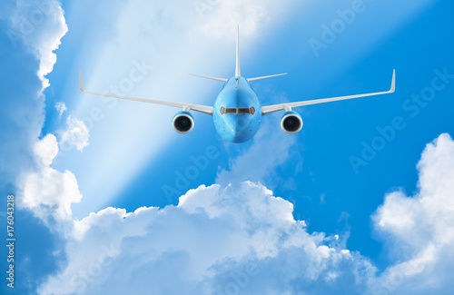 Canvas Print - Airplane flying in the blue sky among clouds and sunlight