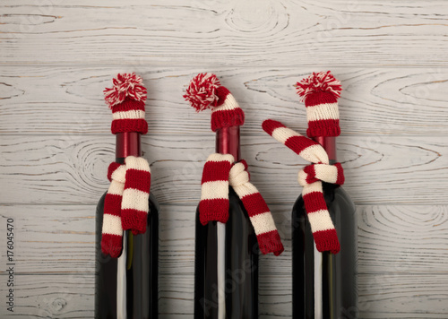 Foto  Merry Christmas and a Happy New Year! Bottles of wine in a knitted cap of Santa Claus