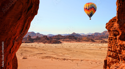 Photo Stands Brown Colorful hot air balloon flight in the blue sky in beautiful landscape of multicolored stony desert with rocks. Timna geological park. Israel