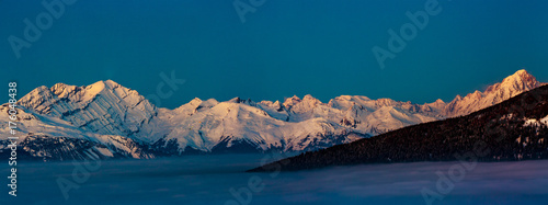 Photo Stands Green blue Scenic panorama sunset landscape of Crans-Montana range in Swiss Alps mountains with peak in background, Crans Montana, Switzerland.
